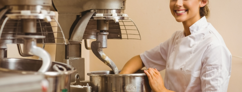Baker using large mixer in a commercial kitchen